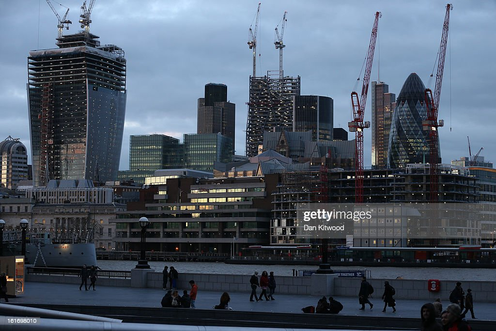 People walk alongside the Thames near City Hall in front of the City of London skyline on February 14, 2013 in London, England.