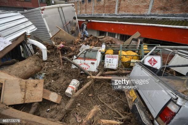 People walk amid the rubble left by mudslides following heavy rains in Mocoa Putumayo department southern Colombia on April 2 2017 Massive mudslides...