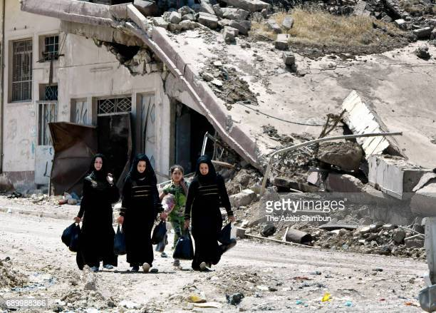 People walk among debris at the area freed from the Islamic States on May 24 2017 in Mosul Iraq