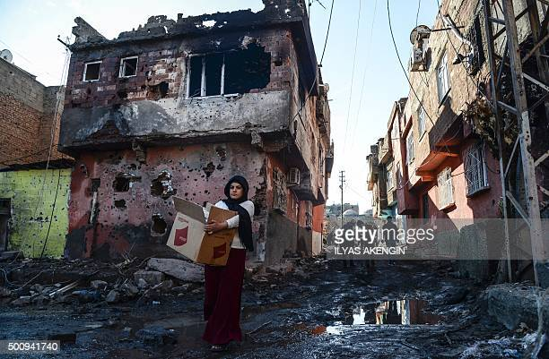 People walk among rubble and damaged buildings in the Sur district in Diyarbakir on December 11 2015 A policeman was killed on December 9 2015 by...