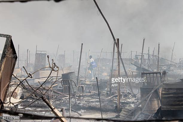 People walk among rubble in an United Nations base in the northeastern town of Malakal on February 18 where gunmen opened fire on civilians...