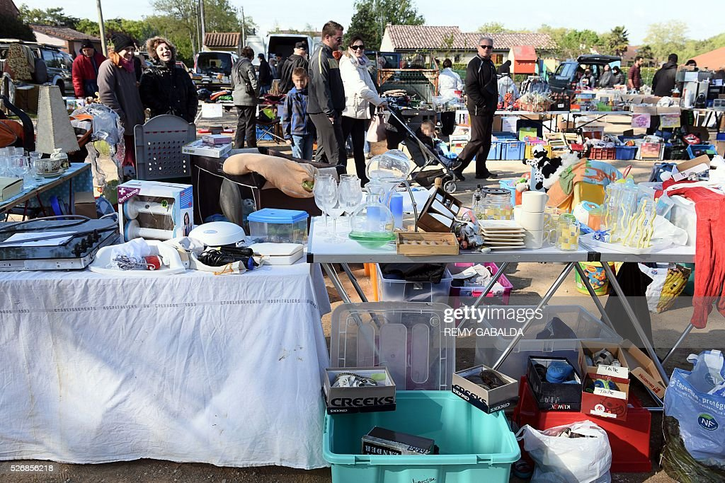 People walk among stalls during the annual car boot sale in Labastide-Beauvoir on May 1, 2016. / AFP / REMY