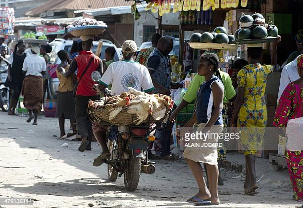 People walk and carry food at the Tokpa market on July 1 in Cotonou French president Francois Hollande is expected tonight for a state visit as part...