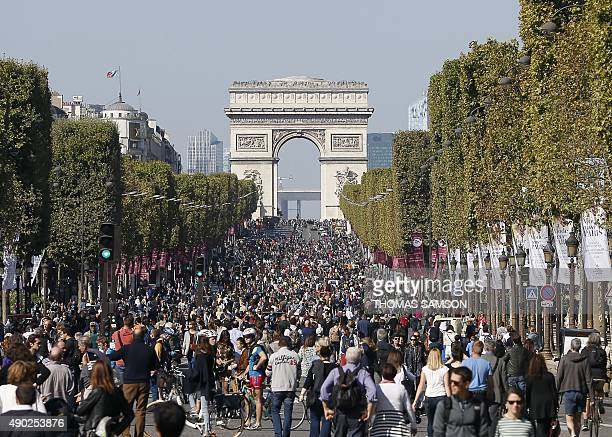 People walk and cycle along the Champs Elysee Avenue during the 'CarFree Day' event taking place in the French capital Paris and organised by the...