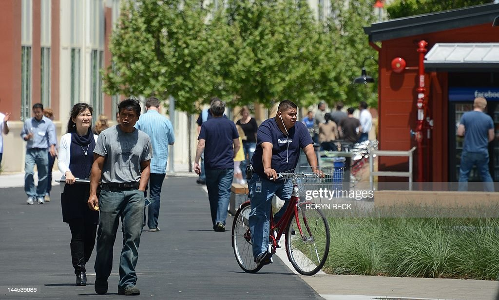 People walk and ride bicycles at the Facebook main campus in Menlo Park, California, May 15, 2012. Facebook, the world's most popular internet social network, expects to raise USD $12.1 billion in what will be Silicon Valley's largest-ever initial public offering (IPO) later this week.
