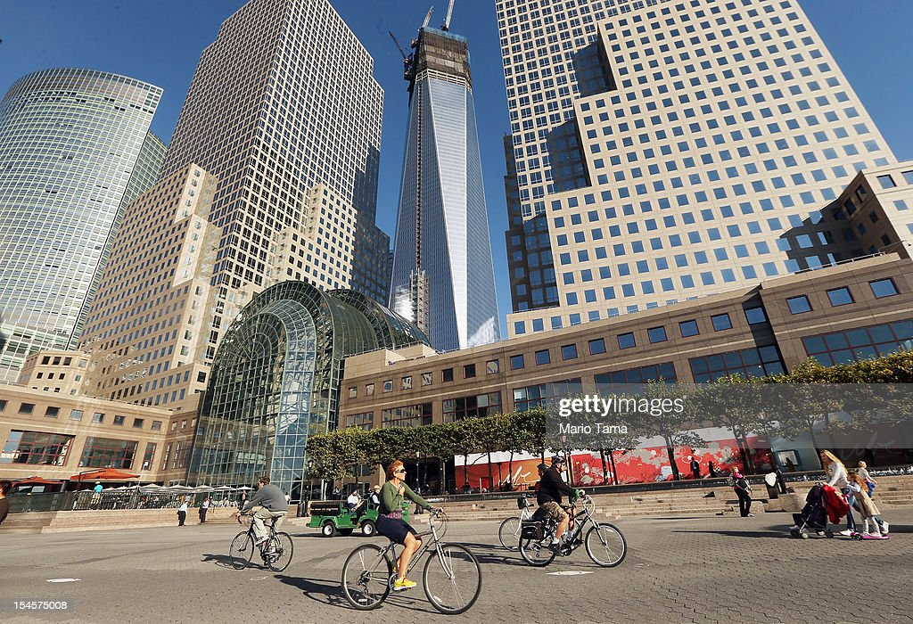 People walk and ride bicycles in front of the World Financial Center in Lower Manhattan as One World Trade Center (C)rises under construction on October 22, 2012 in New York City. The Census Bureau reported last month that between 2000 and 2010 the downtown population grew by nearly 40,000 people, in spite of the September 11 terrorist attacks at the World Trade Center. One World Trade Center is scheduled to open in 2014 at the symbolic height of 1,776 feet and will be the tallest building in the Western Hemisphere.