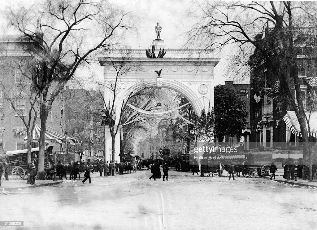 People walk and ride carriages near the arch covered in papiermache wreaths garlands of flowers and American flags in Washington Square Park during...