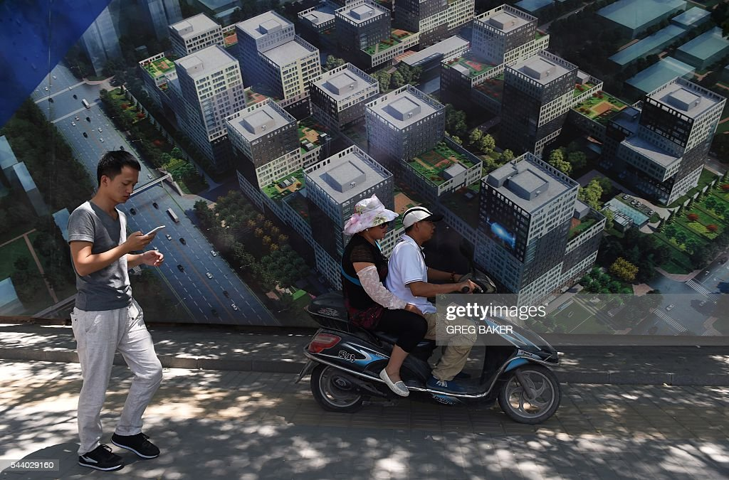 People walk and ride past a billboard advertisement for a commercial and residential complex in Beijing on July 1, 2016. The cost of Chinese new homes rose at a slower rate in June from the previous month, figures showed on July 1, as measures to tame prices in the world's second-largest economy took hold. / AFP / GREG