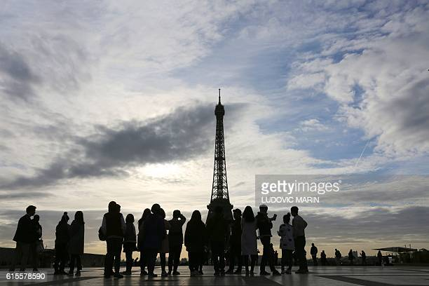 People walk and take pictures on the parvis des droits de l'homme square in front of the Eiffel tower on October 19 2016 in Paris moments after...