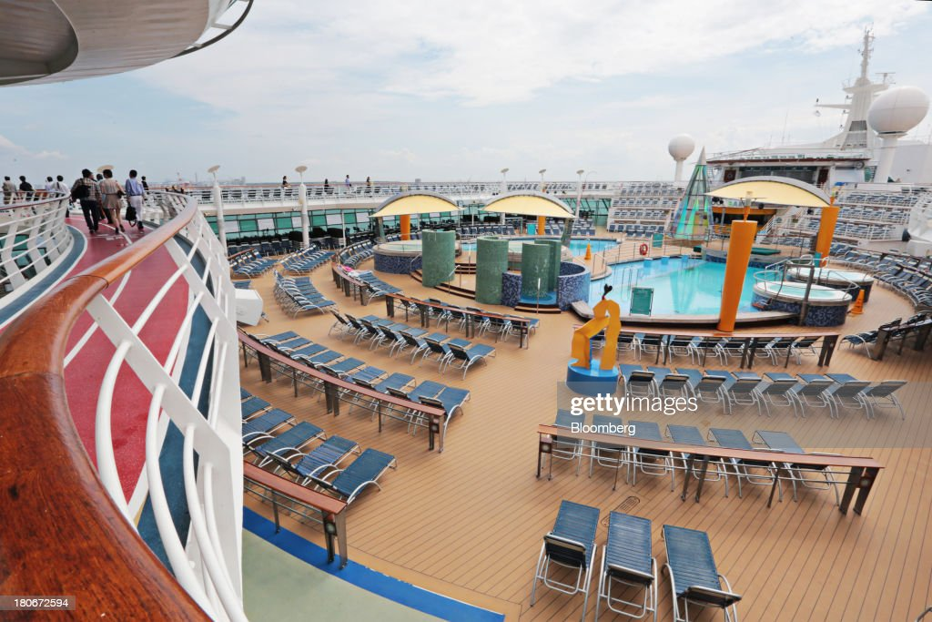 People walk around a deck overlooking recreational facilities aboard the Royal Caribbean Cruises Ltd.'s Voyager of the Seas, berthed at the Ohi wharf in Tokyo, Japan, on Saturday, Sept. 14, 2013. Royal Caribbean, the worlds second-largest cruise-line operator, doubled its dividend and will make directors stand for election every year. Photographer: Yuriko Nakao/Bloomberg via Getty Images
