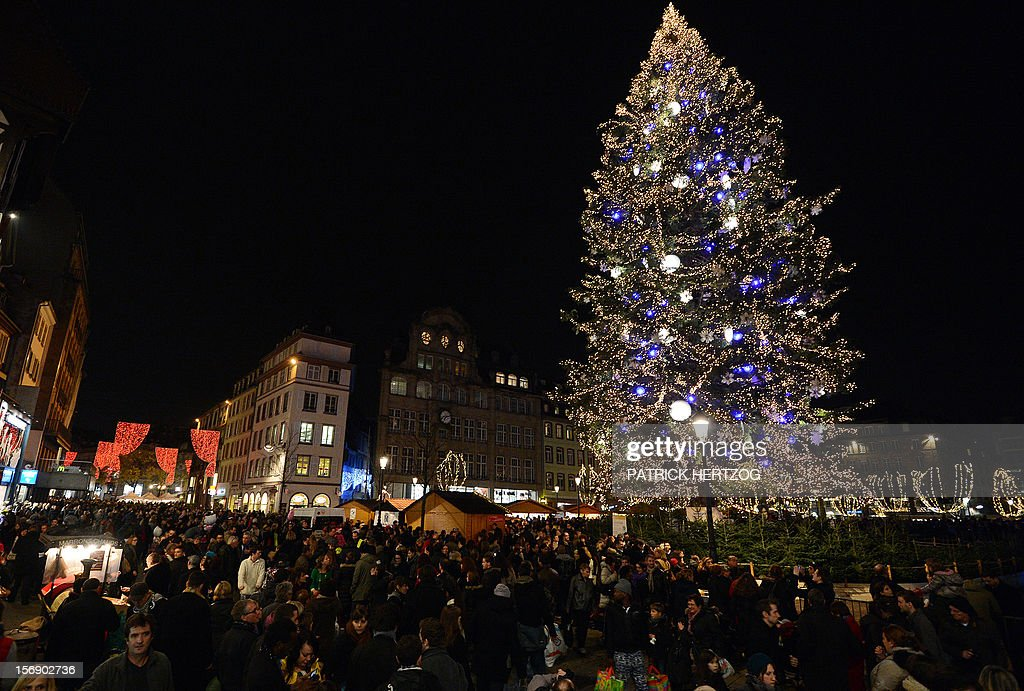 People walk around a giant Christmas tree on November 24, 2012 in Strasbourg, eastern France on the opening day of the city's Christmas market, the largest and one of the eldest French Christmas markets. With over 300 market chalets, Strasbourg attracts over 1.6 million visitors during the Christmas season.