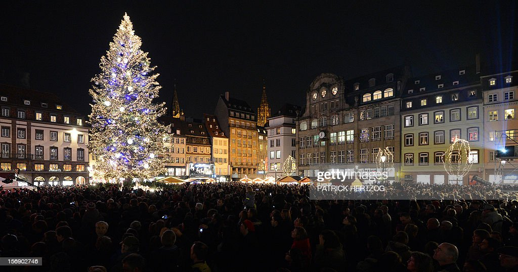 People walk around a giant Christmas tree on November 24, 2012 in Strasbourg, eastern France on the opening day of the city's Christmas market, the largest and one of the eldest French Christmas markets. With over 300 market chalets, Strasbourg attracts over 1.6 million visitors during the Christmas season. AFP PHOTO / PATRICK HERTZOG