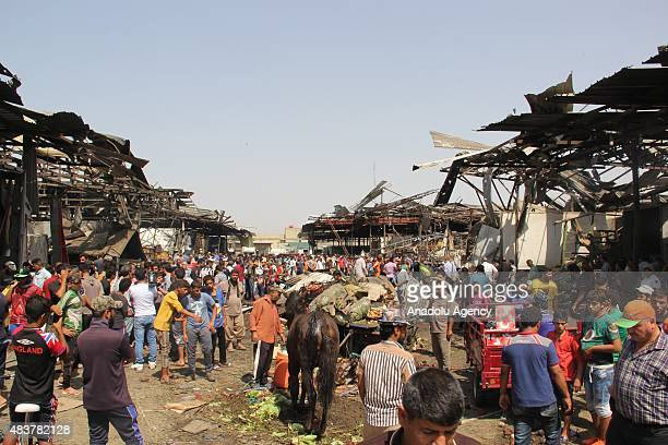 People walk around damaged food market after the bomb attack in Baghdad Iraq on August 13 2015 At least 45 people were killed and 105 were injured...
