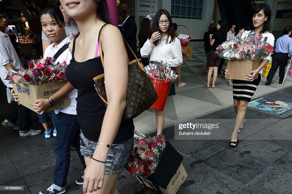 People walk around Raffles Place to sell flowers during Valentine's Day on 14 February, 2013 in Singapore. Valentine's Day is a time to celebrate love, romance and friendship and is celebrated worldwide annually in different ways on February 14.