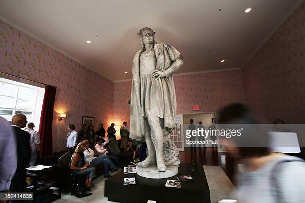 People walk around the 13foot statue of Christopher Columbus stands in the 810squarefoot 'living room' art installation by Japanese artist Tatzu...