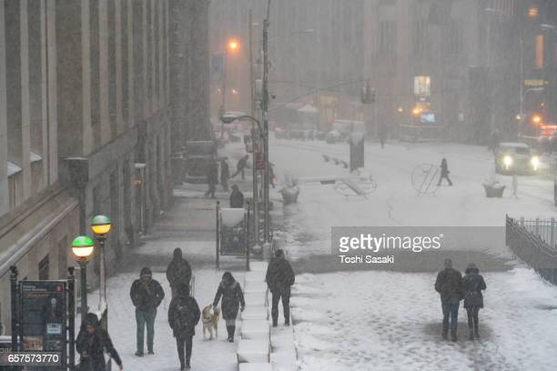 People walk around the New York Stock Exchange during the snowstorm on Feb. 09 2017 at NYC.