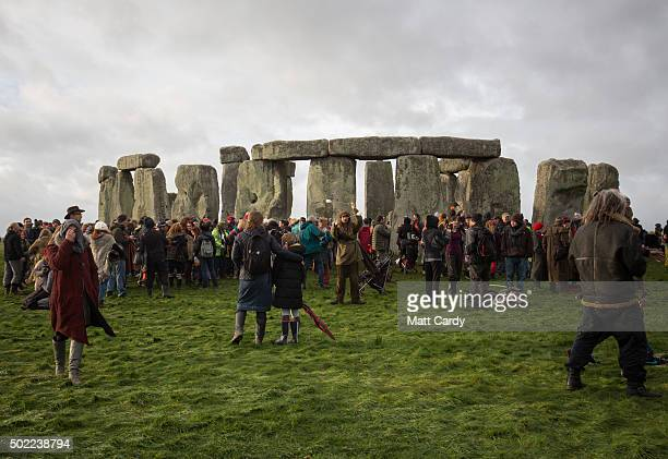 People walk around the outside of the stones as druids pagans and revellers gather in the centre of Stonehenge hoping to see the sun rise as they...