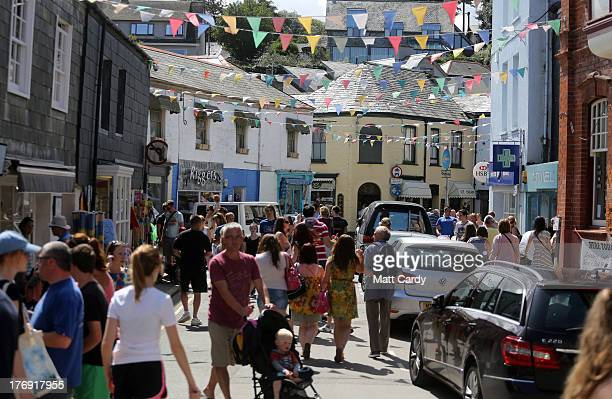 People walk around the shops cafes and restaurants in a street near the harbour on August 19 2013 in Padstow England Over recent years the...
