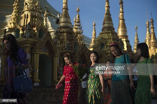 People walk around the Shwedagon Pagoda at sunrise in Yangon on November 6 2015 The former juntaruled country goes to the polls on November 8 in...