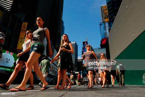 People walk around Times Square during a sunny day as hot temperatures continue in New York on July 21 2017 / AFP PHOTO / EDUARDO MUNOZ ALVAREZ