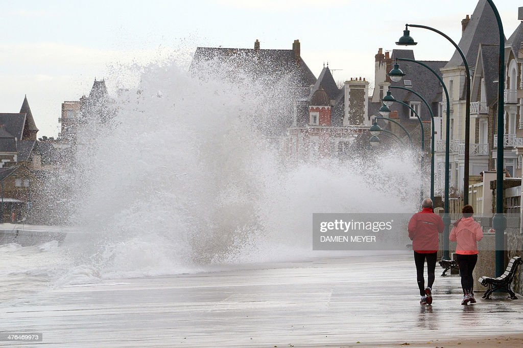 People walk as waves crash against the seawall on the coast of SaintMalo western France on March 3 2014 Due to high tides scheduled late today 11...