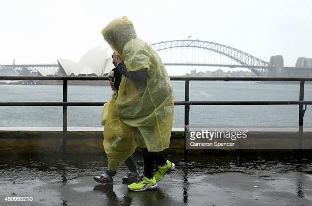 People walk at Mrs Macquarie's Chair in the rain as a major low pressure system covers the east coast of Australia on July 17 2015 in Sydney...