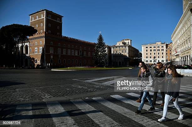 People walk at Piazza Venezia in Rome on December 28 2015 Every vehicle with a uneven number plate is forced off the road as Italian authorities...
