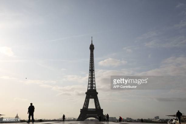 People walk at sunrise on the Human Rights square in front of the Eiffel tower on September 6 in Paris / AFP PHOTO / LUDOVIC MARIN