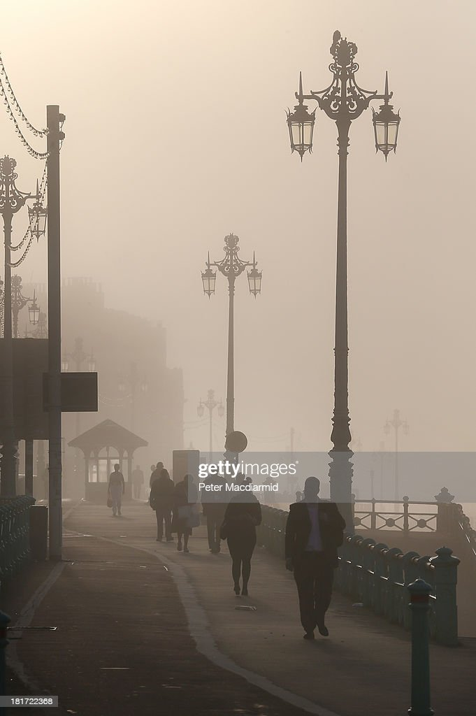 People walk at sunrise through the fog on the seafront opposite the Labour Party conference on September 24, 2013 in Brighton, England. Party leader Ed Miliband will deliver a keynote speech to delegates later.