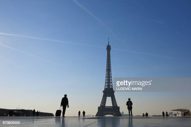 People walk at sunrise through the Human Rights plaza facing the Eiffel Tower at the Trocadero on April 20 2017 in Paris / AFP PHOTO / Ludovic MARIN