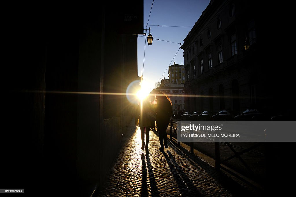 People walk at Terreiro do Paco in Lisbon during a sunny day on February 28, 2013.