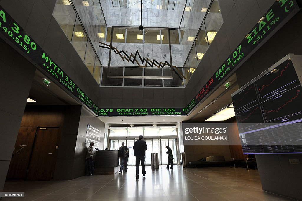 People walk at the Athens stock exchange on October 27 2011 Greece reacted with measured relief on Thursday after European leaders sealed a deal to...