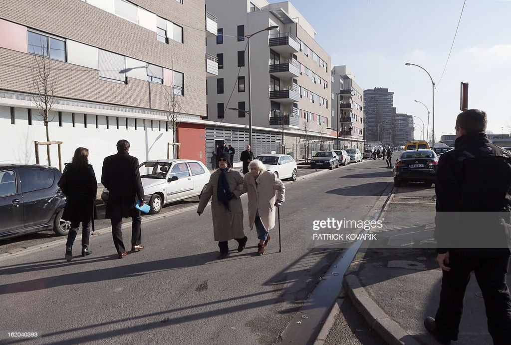 People walk at the La Forestiere housing estate in Clichy-sous-Bois, northern suburb of Paris, on February 18, 2013.