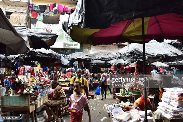People walk at the large market of Adjame a popular district of Abidjan on August 10 2017 The Ivorian government in a council of ministers on July 26...