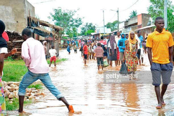 People walk barefoot through Buterere northwest of Bujumbura on March 17 after overnight torrential rains destroyed more than 100 houses and resulted...
