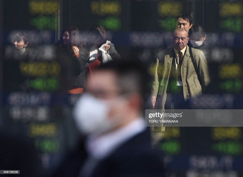 People walk before an electric quotation board flashing share prices of the Tokyo Stock Exchange (TSE) in front of a securities company in Tokyo on February 9, 2016. Tokyo shares tumbled nearly five percent, extending a global sell-off as a stronger yen dented exporters and after oil prices tanked again on fears of a deepening economic slowdown. AFP PHOTO/Toru YAMANAKA / AFP / TORU YAMANAKA