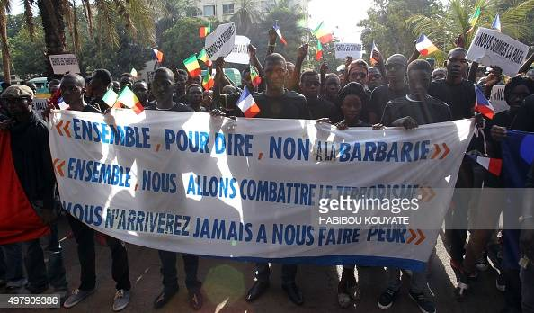 People walk behind a banner reading 'Together to say no to barbarism Together we will fight terrorism You will never scare us' holding French and...