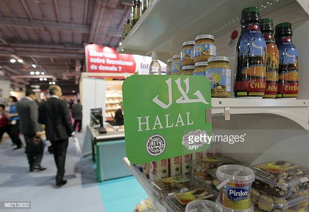 People walk behind a stand of Halal food products on March 31 2010 shown during the Halal expo part of the 'Foodsgoods' fair at the Porte de...