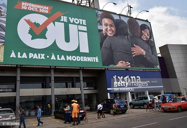People walk below a giant billboard with the slogan reading 'Referendum October 30 2016 I vote 'yes' for freedom and modernity' in Abidjan on October...