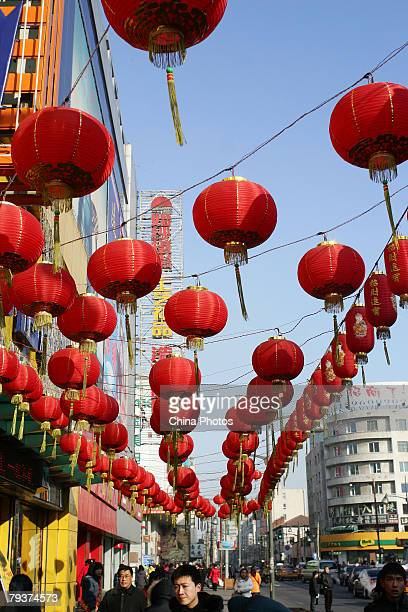 People walk below red lanterns installed for the Chinese lunar new year alond a street on January 30 2008 in Changchun of Jilin Province China The...