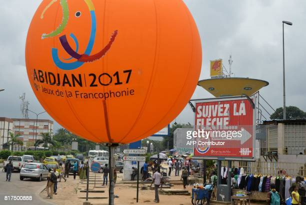 People walk beneath a giant balloon reading 'Abidjan 2017 8th Frenchspeaking countries Games on June 27 2017 in Abidjan ahead of the Jeux de la...