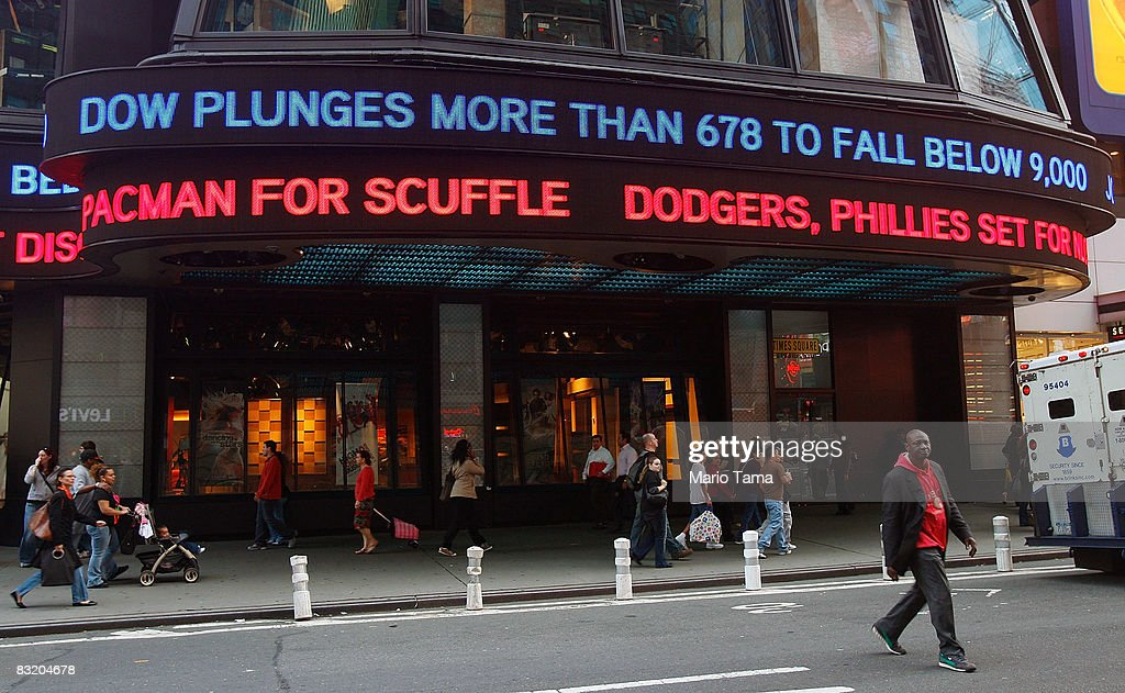 People walk beneath a Times Square news ticker reading 'Dow Plunges More Than 678 To Fall Below 9000'' October 9 2008 in New York City The Dow Jones...