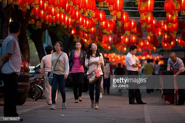 People walk beneath lanterns on a street ahead of the Mid Autumn Festival in Beijing on September 26 2012 Traditionally recognized as a symbol of...