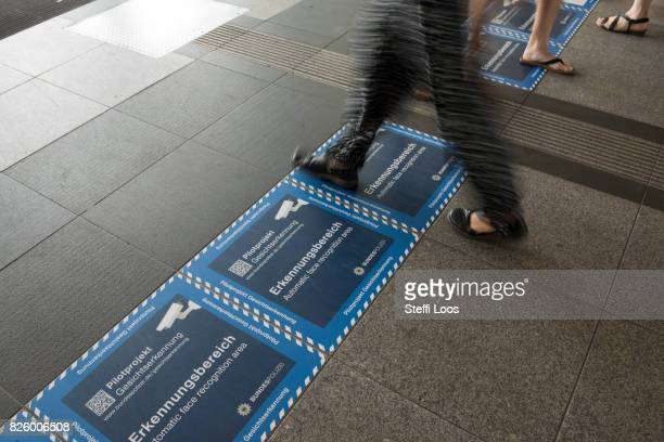 People walk beside information signs which make passersby aware of a facial recognition technology test at Berlin Suedkreuz station on August 3 2017...