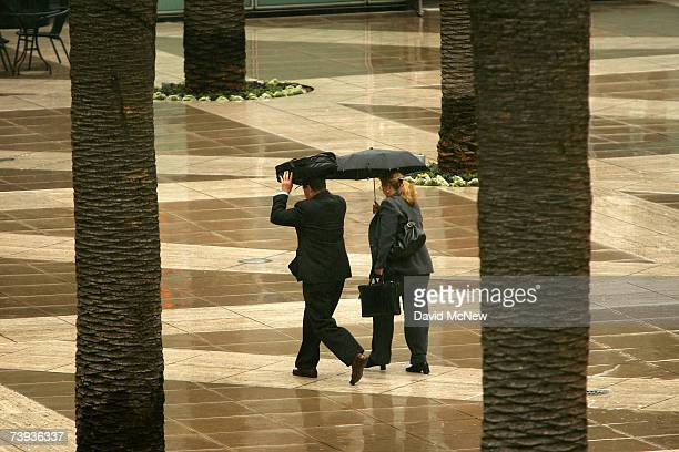 People walk between palm trees in the rain as a lateseason Pacific storm brings rain and snow to southern California April 20 2007 in Los Angeles...