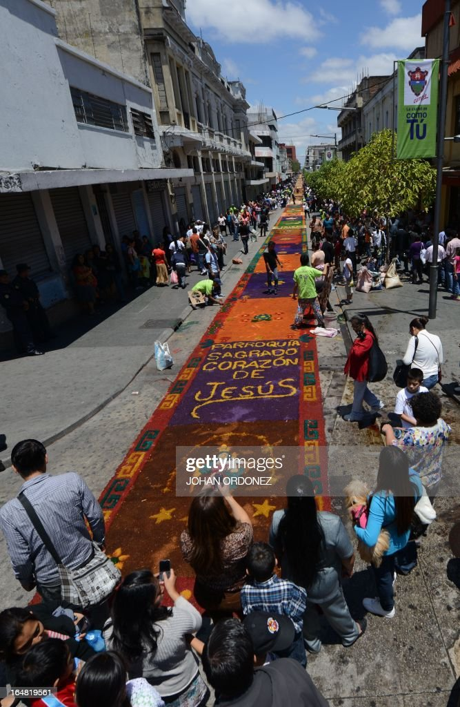 People walk by a 1,400 meters carpet of flowers and colored sawdust, made by municipal employees and volunteers in an attempt to set a Guinness World Record for the longest carpet of the world, in Guatemala City on March 28, 2013. These carpets are traditionally made during Hoy Week each year. AFP PHOTO / Johan ORDONEZ