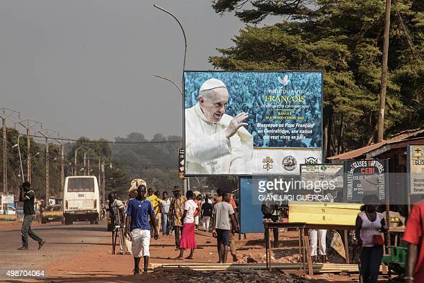 People walk by a billboard welcoming Pope Francis ahead of his visit in Bangui on November 25 2015 Pope Francis on November 25 warned of the need to...