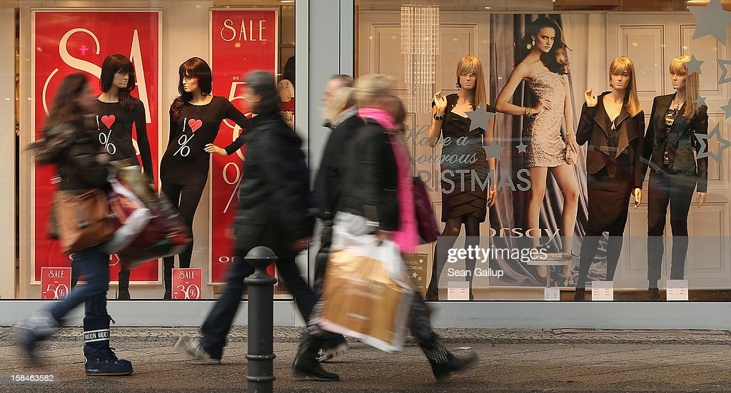 People walk by a clothing store adevertising sales on a shopping street in Steglitz district on December 17, 2012 in Berlin, Germany. Retailers are hoping for a strong Christmas season in Germany, one of the few countries whose economy has so far weathered the current Eurozone debt crisis relatively well.