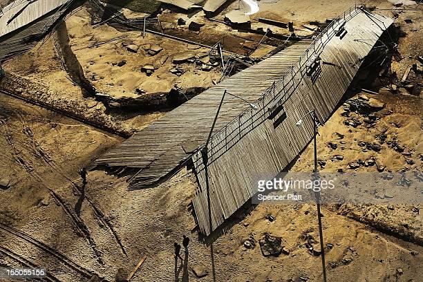 People walk by a destroyed section of the Rockaway boardwalk in the heavily damaged Rockaway section of Queens after the historic boardwalk was...