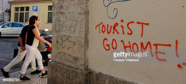 People walk by a graffiti opposing tourism written on a wall in Travessa da Ribeira Nova Cais do Sodre on October 31 2017 in Lisbon Portugal Large...